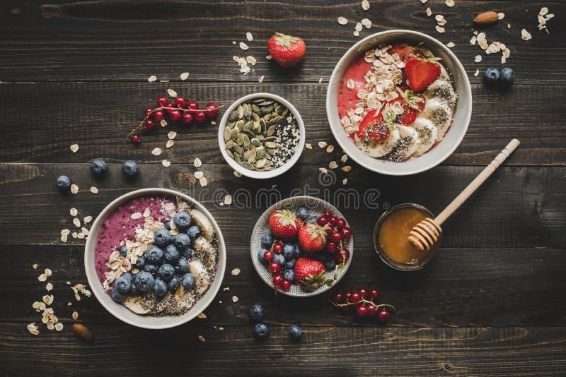 Bowlar den läckra smoothien för den Helthy frukosten med frukter, bär och frö på träbakgrunden royaltyfria foton