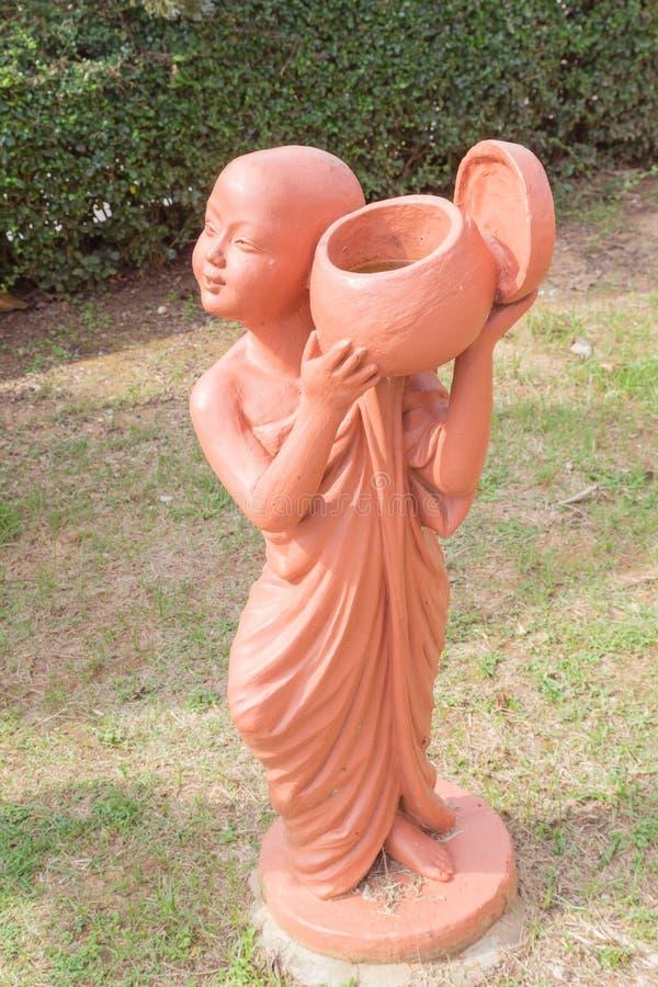 Bowlar hållande allmosa för buddistisk novis leradockan på den thailändska buddistiska templet royaltyfria bilder