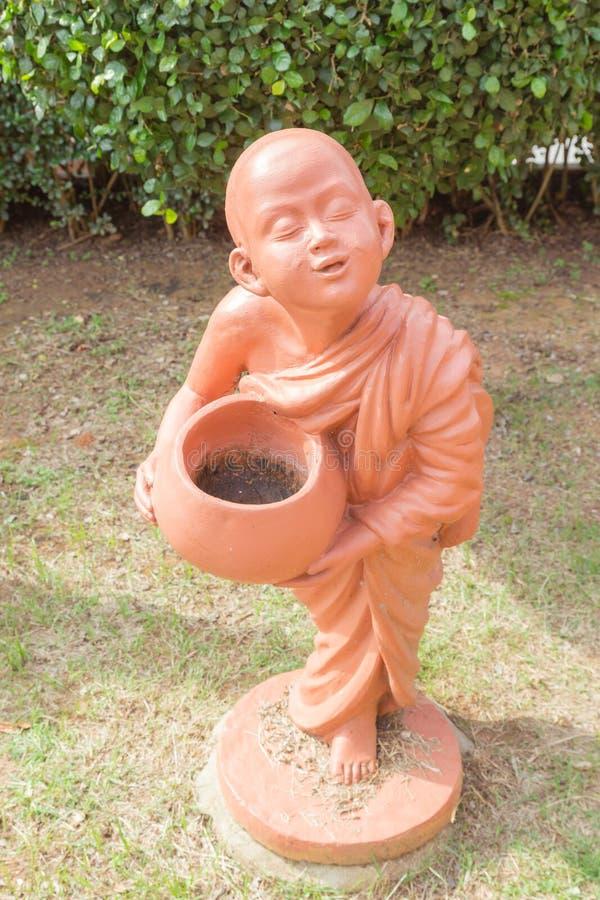 Bowlar hållande allmosa för buddistisk novis leradockan på thailändsk buddistisk tem royaltyfri bild
