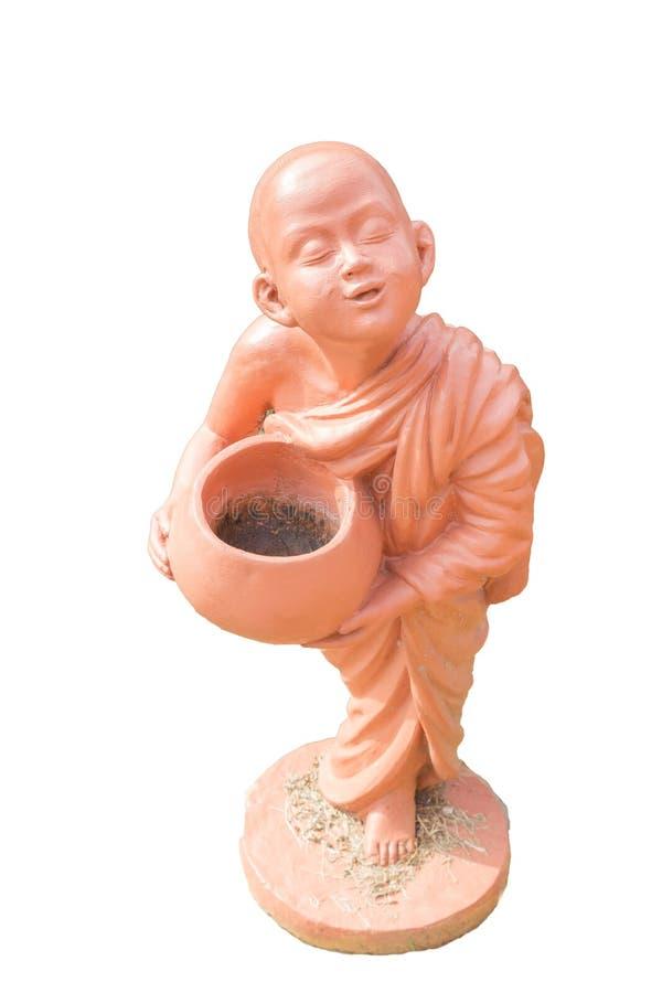 Bowlar hållande allmosa för buddistisk novis leradockan som isoleras på vit arkivfoton