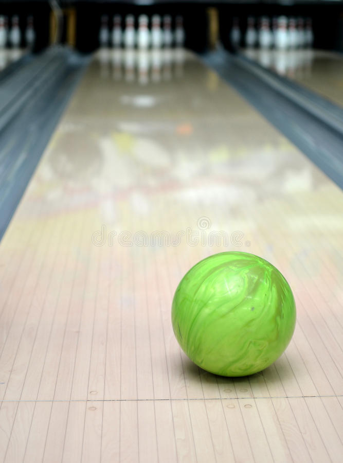 Bowling ball. Green ball on the background of pins royalty free stock image