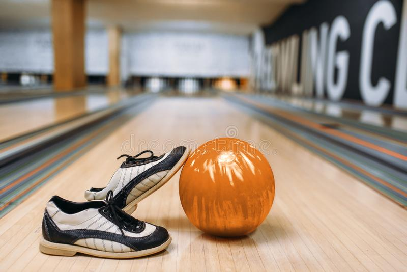 Bowling ball and house shoes on wooden floor. In club, pins on background, nobody. Bowl game concept, tenpin royalty free stock photos