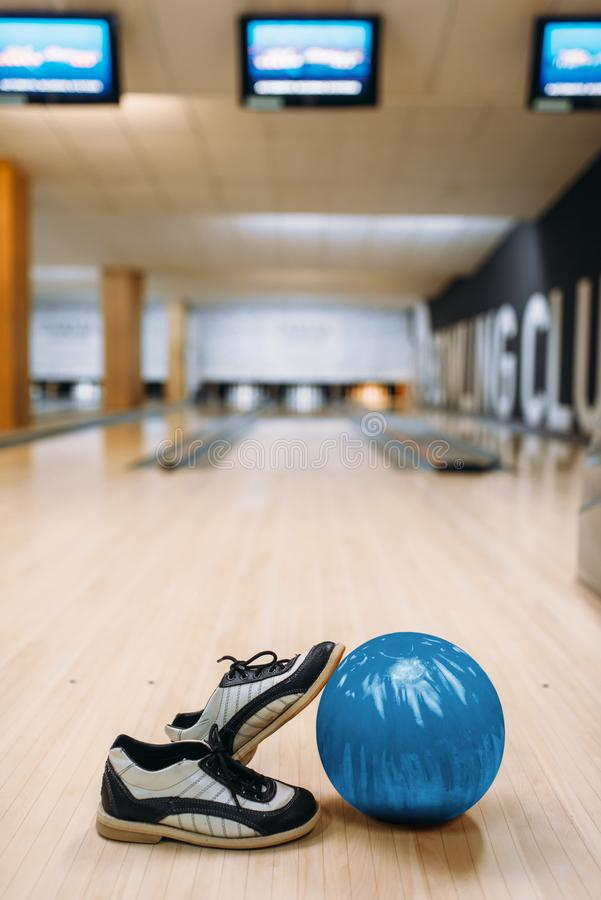 Bowling ball and house shoes on wooden floor. In club, pins on background, nobody. Bowl game concept, tenpin stock image