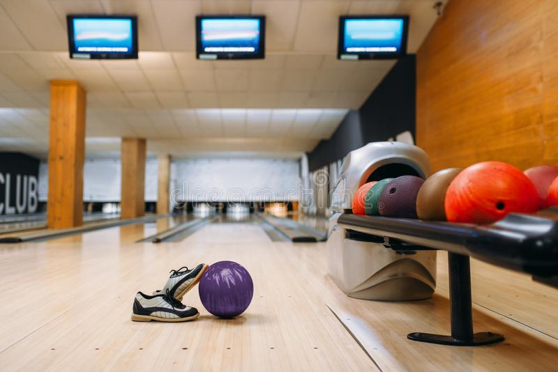 Bowling ball and house shoes on wooden floor. In club, pins on background, nobody. Bowl game concept, tenpin stock photo