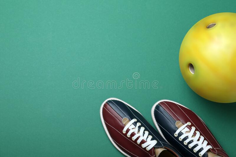 Bowling ball and shoes on background, flat lay. Space for text. Bowling ball and shoes on green background, flat lay. Space for text stock photos