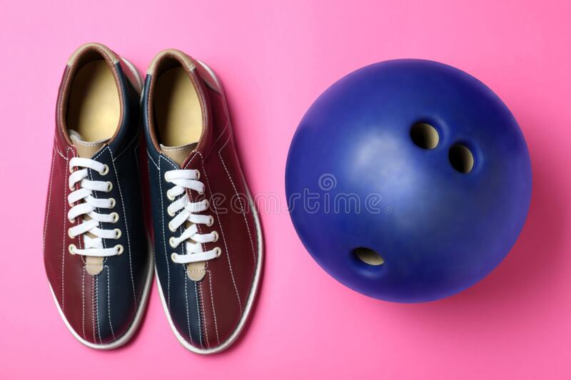 Bowling ball and shoes on pink background. Flat lay royalty free stock photography