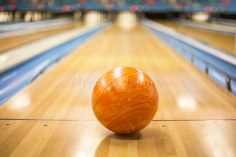 Bowling ball sitting in a colorful bowling alley lane. Close up view of an orange Bowling ball sitting in a colorful bowling alley lane royalty free stock photo
