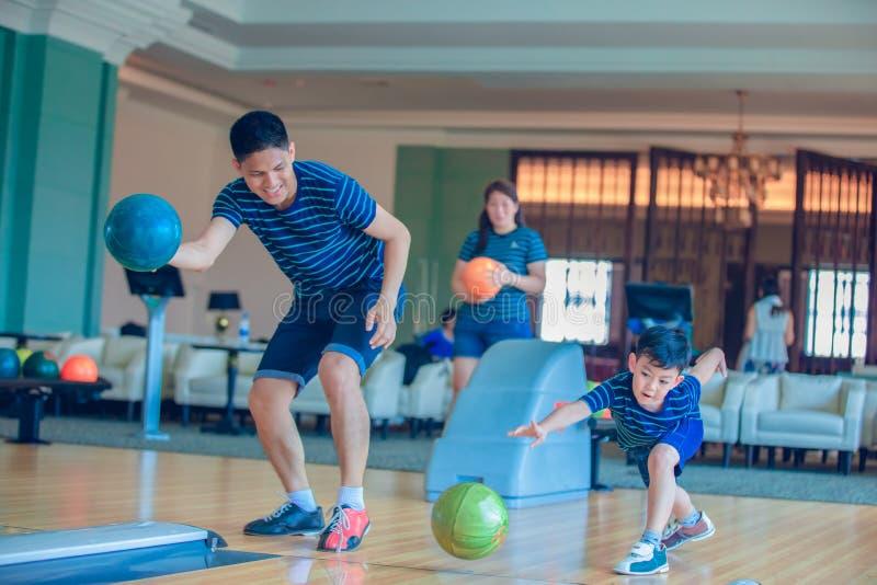 Bowling d'istruzione del gioco del figlio e della famiglia del padre al club lanciante sopra rilassarsi tempo fotografie stock libere da diritti