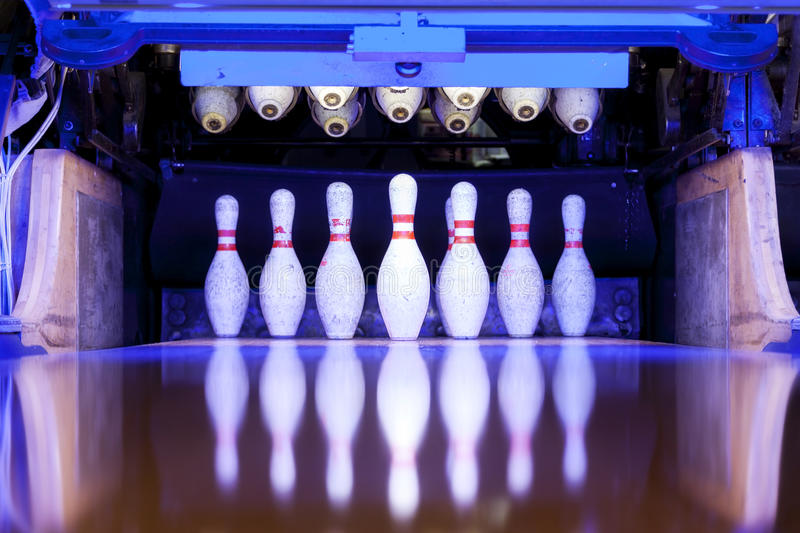 Bowling pins ready to be felled on the track. Reflected in the floor royalty free stock photos