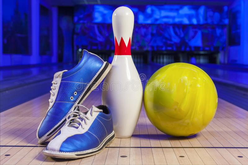 Bowling shoes and bowling ball on the game track close-up. Bowling shoes and ball for playing the bowling game on track for a bowling game closeup stock photo