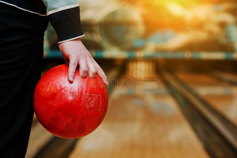 Bowlingklot på handen av manbakgrundsbowlingbanan royaltyfri fotografi