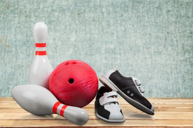 Bowlingskor och boll på bakgrund royaltyfri bild