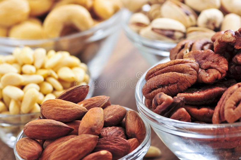 Bowls of assorted nuts. Many glass bowls of almonds walnuts pistachios and pine nuts royalty free stock photo