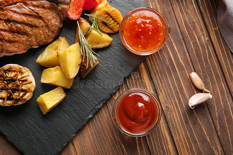 Bowls of barbecue and chili sauce with grilled meat and potato on wooden table stock image