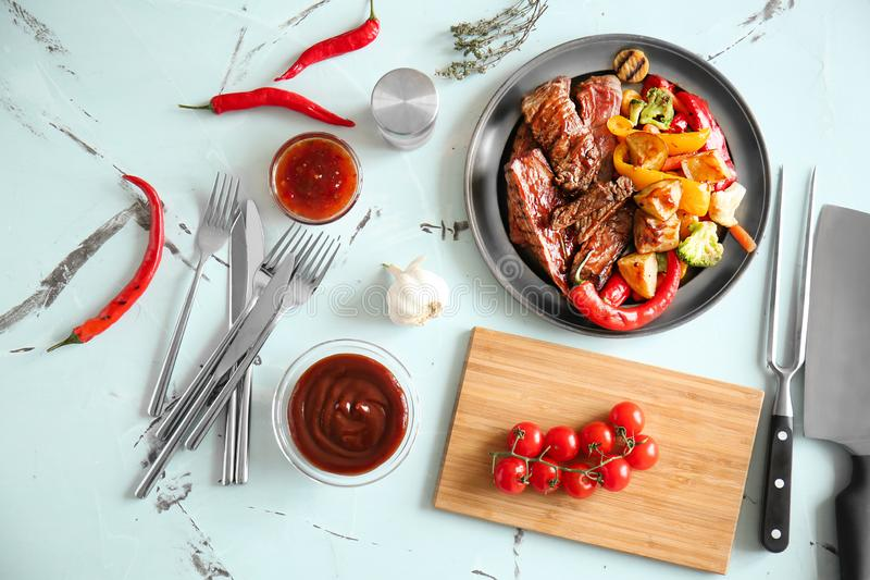 Bowls of barbecue and chili sauce with grilled meat on table stock image