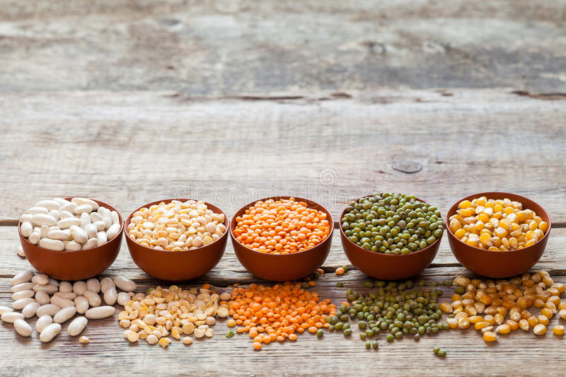 Bowls of cereal grains. Red lentils, green mung, corn, beans and peas on wooden table royalty free stock photos