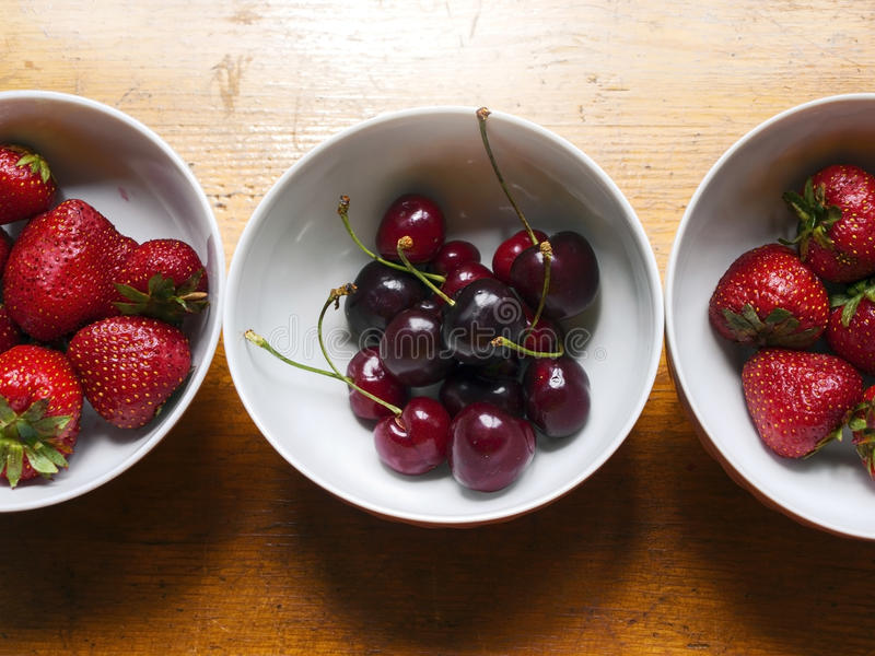 Bowls of cherries and strawberries stock images