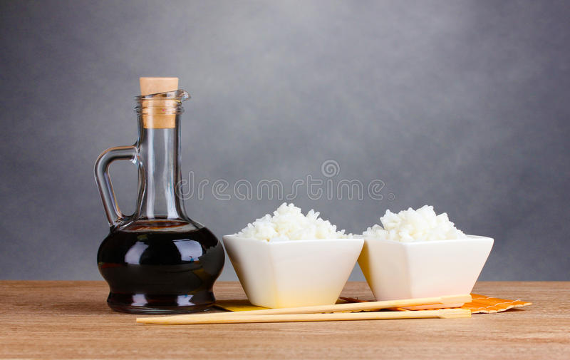 Bowls of cooked rice and soy sauce in jar. On wooden table on gray background royalty free stock photo