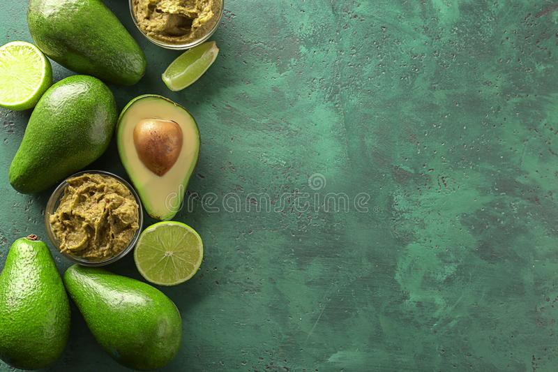 Bowls with delicious guacamole, lime and ripe avocados on color textured background royalty free stock image