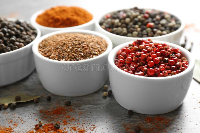 Bowls with different ground pepper and corns on grey table stock photos