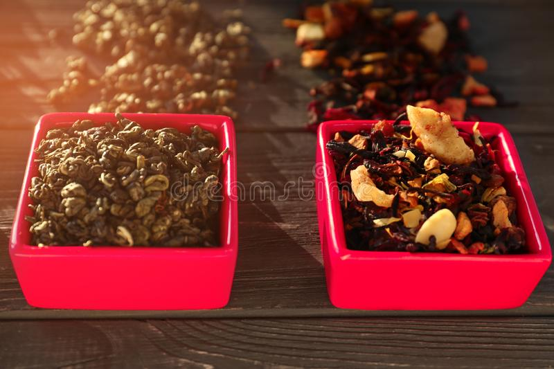 Bowls with different types of dry tea leaves on wooden background royalty free stock photography