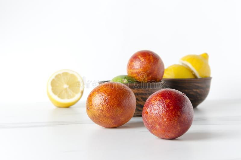 Bowls full of fresh and juicy fruits.Blood oranges, lemons and lime in white table against white background royalty free stock images