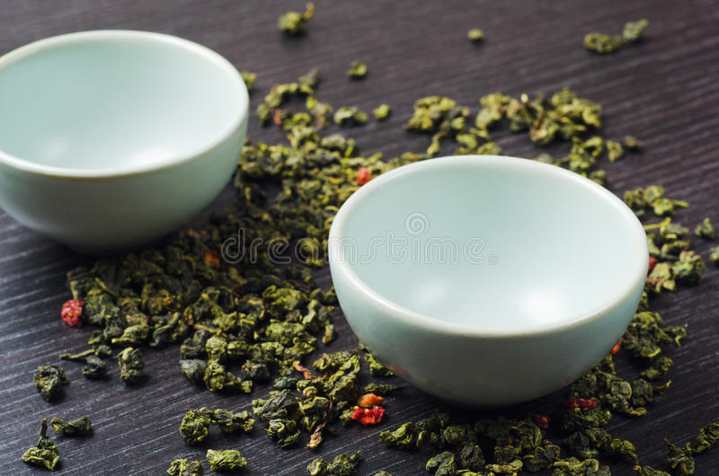 Bowls with green oolong tea and strawberries stock photos