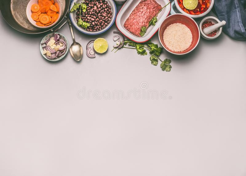 Bowls with ingredients for balanced one pan meal with beans, minced meat, rice and cut vegetables. On gray background, top view, border or food background stock photography