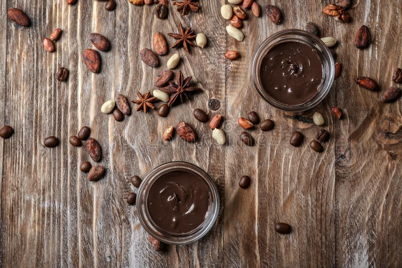 Bowls with molten chocolate with nuts and beans on wooden table royalty free stock photography