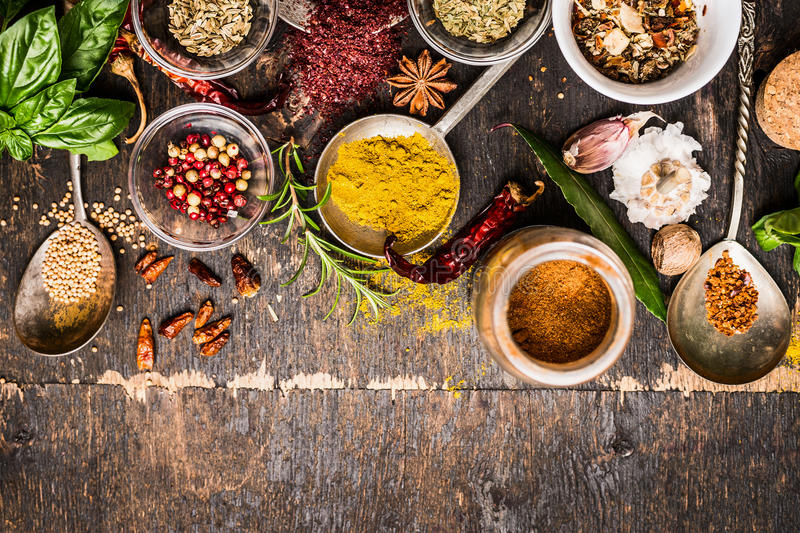 Bowls and spoon of Various spices selection on rustic wooden background, top view stock photography