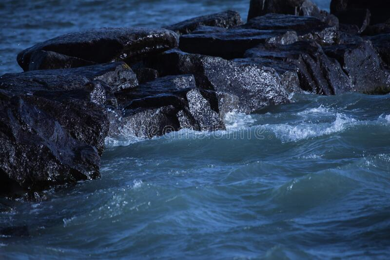 The Stones Glisten From The Lake Water. Bluish green water splashes against the stone making them glisten under the sunny sky royalty free stock images