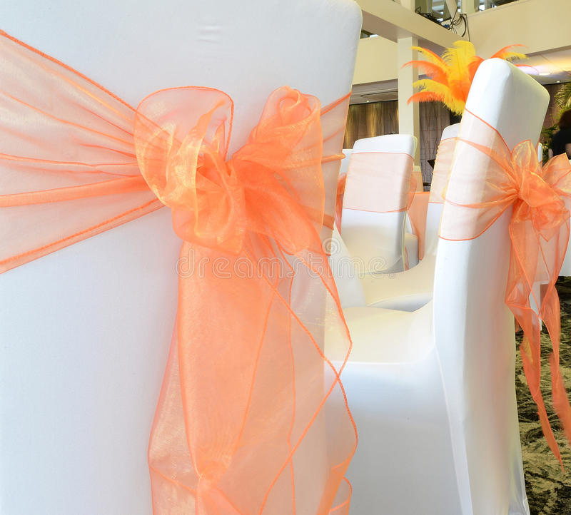 Bows tied to chairs at a wedding. Colorful orange bows tied to the backs of white chairs at a wedding ceremony royalty free stock photography