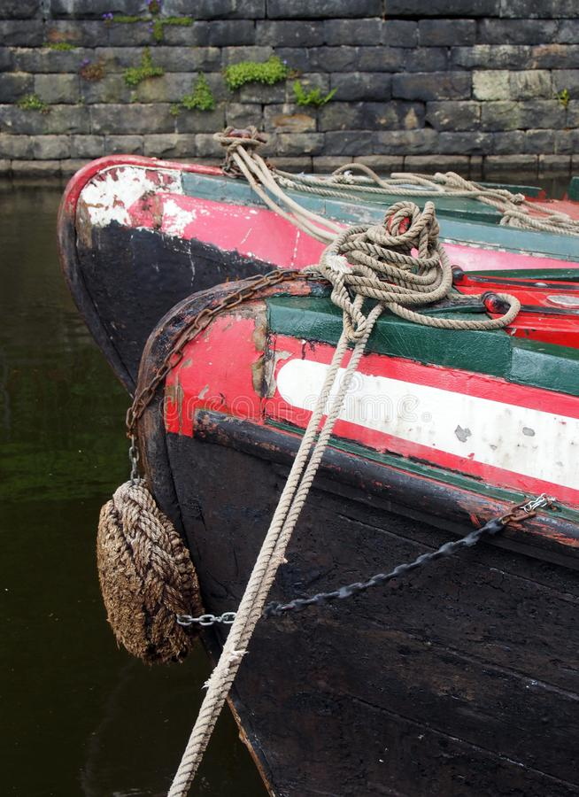 Bows of two traditional old narrow boats moored on a canal surrounded by a stone wall. The bows of two traditional old narrow boats moored on a canal surrounded stock images