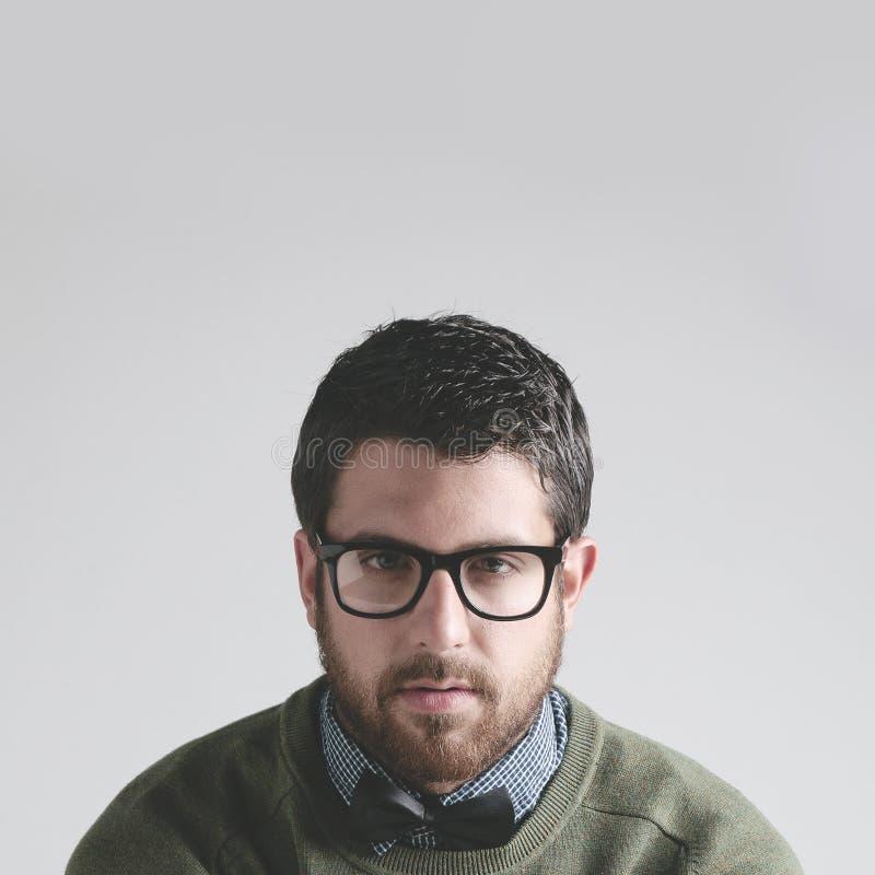 Bowtie que lleva elegante y vidrios del hombre joven en fondo gris. imagen de archivo