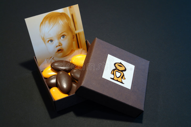 Box with baby portrait, sugared almonds and chocolates. Birth announcement box with baby portrait, sugared almonds and chocolates royalty free stock photography