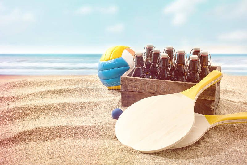 Box of beers with bat and a ball on a beach. Box of beers with two wooden bats and a colorful volley ball on a beach alongside the ocean conceptual of a summer stock photos