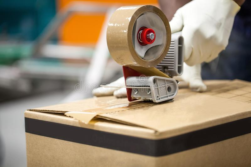 Box being taped shut in packaging plant. Parcel tape closing box in manufacturing plant royalty free stock photos