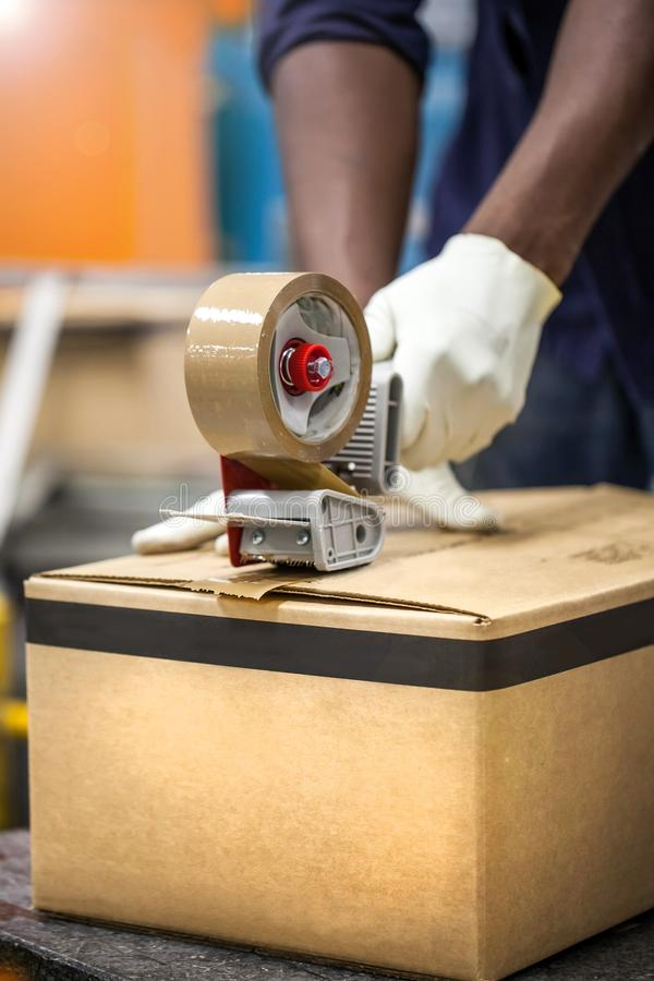 Box being taped shut. Box being taped shut in packaging plant. cardboard box being tapped shut with tape stock images