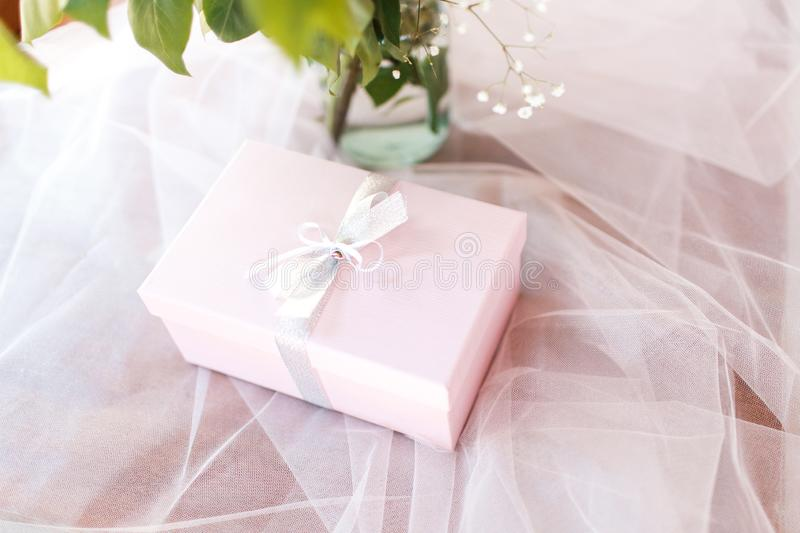 The box with a bow lies on tulle royalty free stock photo