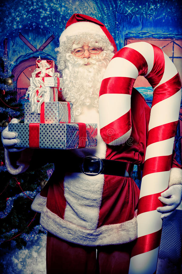 Box and candy. Santa Claus posing with presents over Christmas background stock images