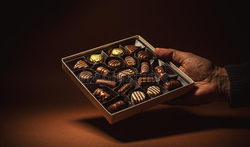 Box Chocolates in a Hand. Male hand is holding an open box of chocolates stock photos