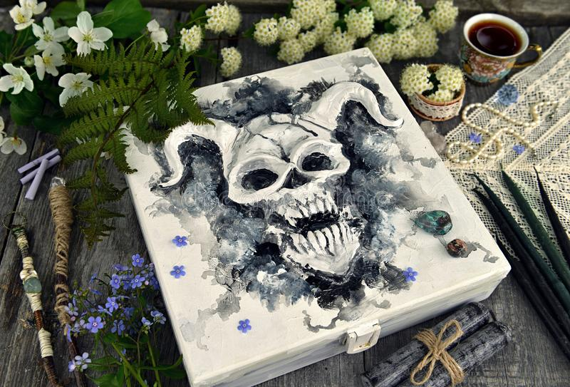 Box with devil face and magic objects with flowers royalty free stock image