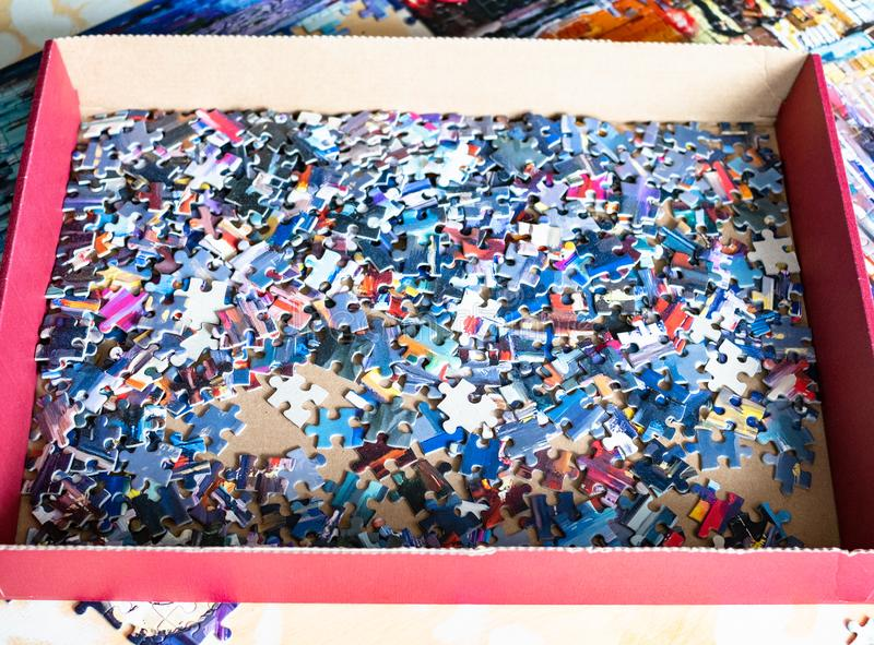 Box with disassembled jigsaw puzzle board game. On table with partly assembled puzzle stock photography
