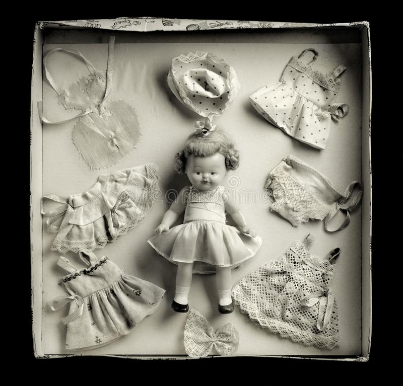 Box doll and dresses game. Vintage box doll game in a dark ambiance. Medium format film photography shot with a warm tone stock photography