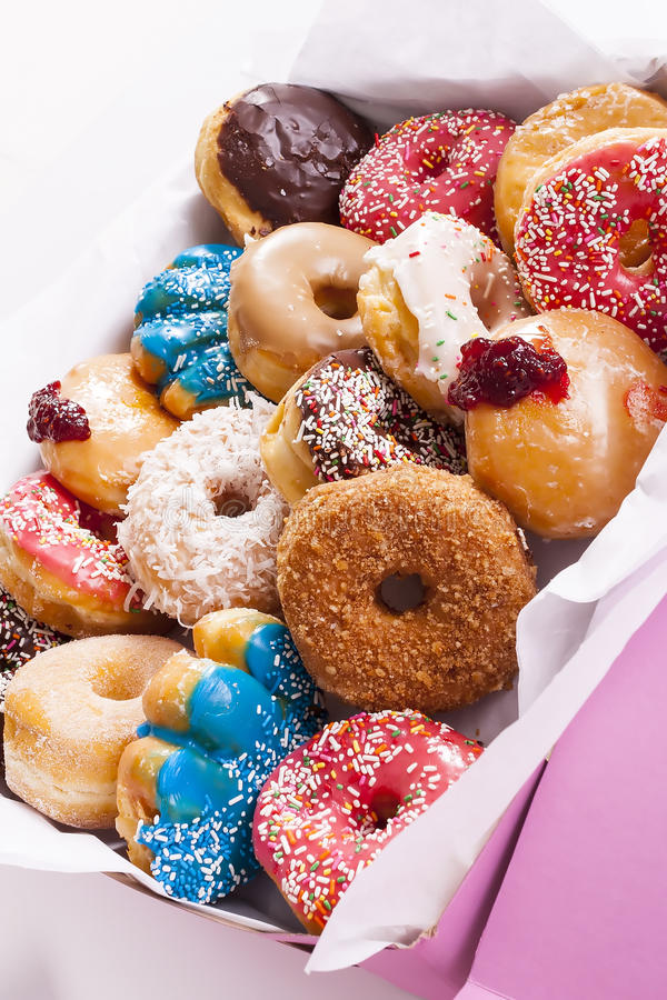 Box of donuts. Close up on box of assorted donuts with frosting, powder and sprinkles royalty free stock image