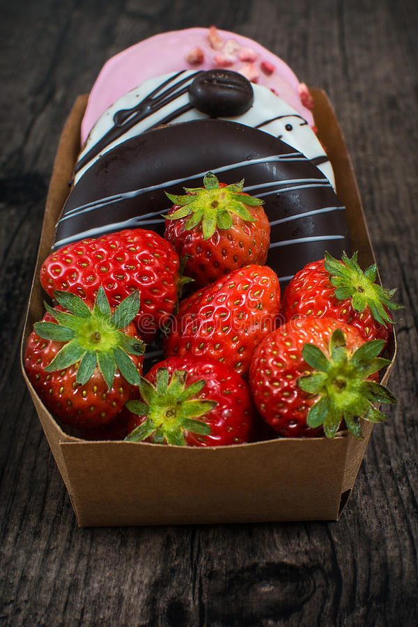 Box of donuts and strawberry over the wooden background royalty free stock photography