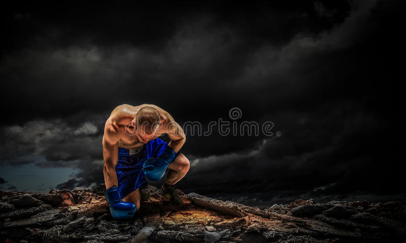 Box fighter trainning outdoor . Mixed media . Mixed media. Strong fighter in shorts against dark sky background. Mixed media royalty free stock image