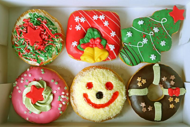 Box Filled with Colorful Christmas and Festive Decorated Doughnuts Sweets stock image