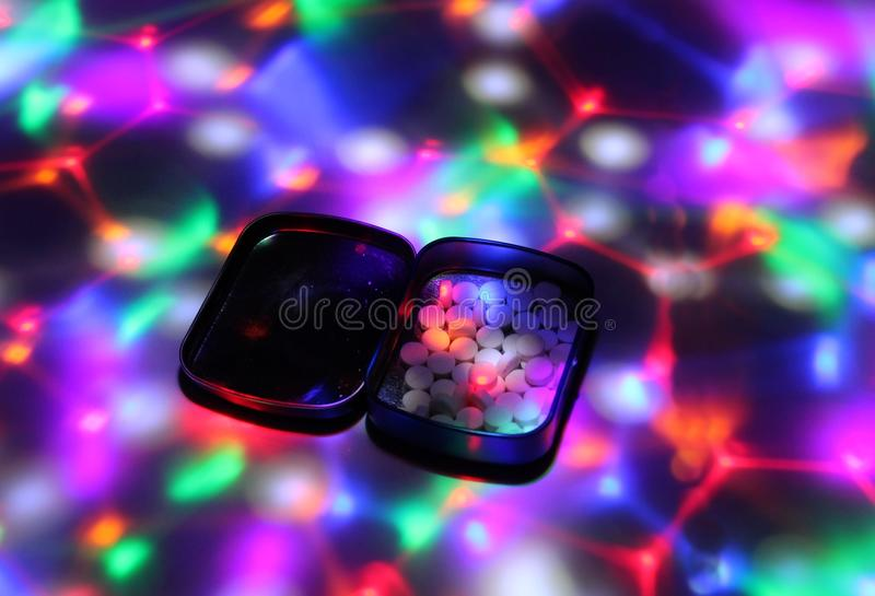A box filled with ecstasy under disco lights. stock photo