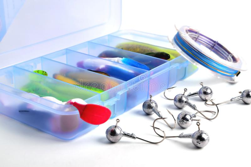 Box for fishing accessories with silicone baits inside, Jig hooks, braided reel on a white background. Close-up stock photos